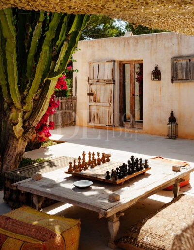 playing chess below the nature and flowers of the garden of villa casanita for rent in sant Francesc, formentera